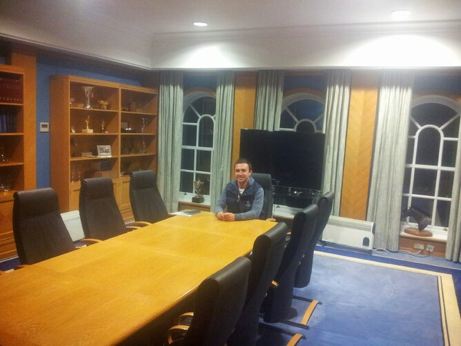 At the head of Shadwell's boardroom table surrounded by bookcases full of trophies. The TV behind me is for Sheikh Hamdan to take part in meetings